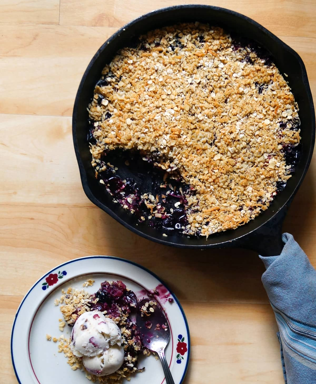 A cast iron skillet filled with the finished cherry and berry crumble beside a small plate with the berry crumble served with ice cream.