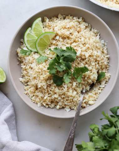 Top down of the cooked cauliflower rice in a gray bowl with slices of lime and cilantro.