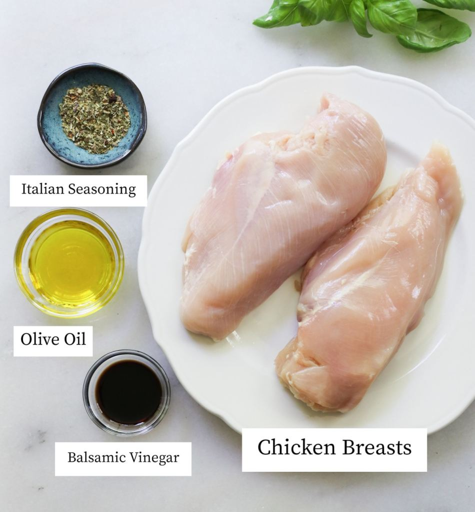 Chicken, italian seasoning, olive oil, and balsamic vinegar on a white marble board, labeled.