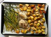 Top down of a large sheet-an topped with cooked chicken breasts, roasted potatoes, and roasted asparagus.