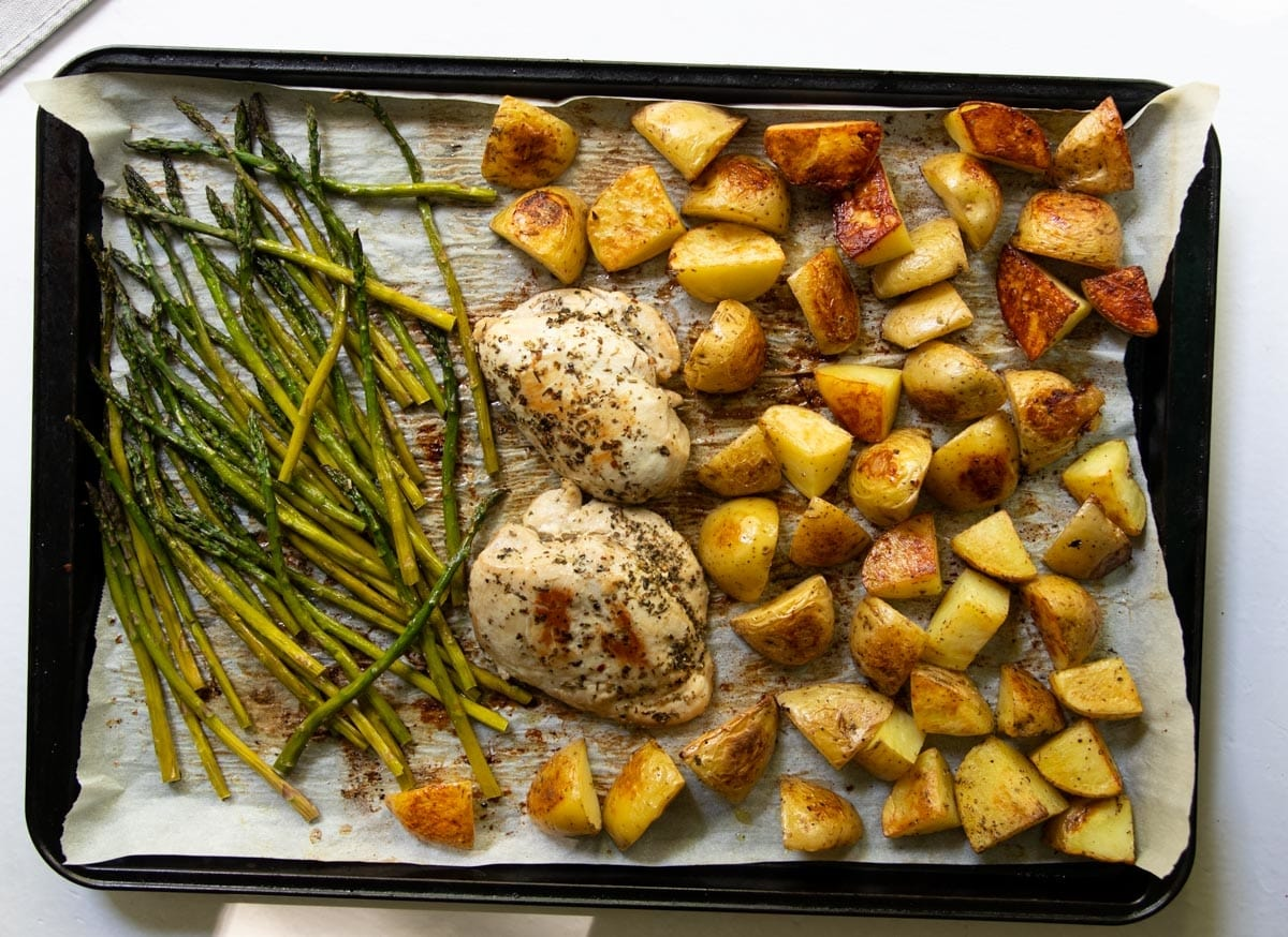 Top down of a sheet-an topped with cooked seasoned chicken breasts, roasted potatoes, and asparagus.