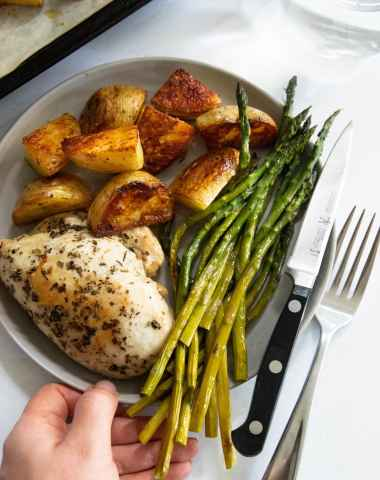 A hand holding a small gray plate with a chicken breast, asparagus, and potatoes.