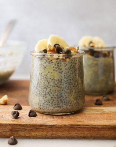 Close up side view of banana chia pudding in a jar topped with chocolate chips, walnuts, and banana slices.