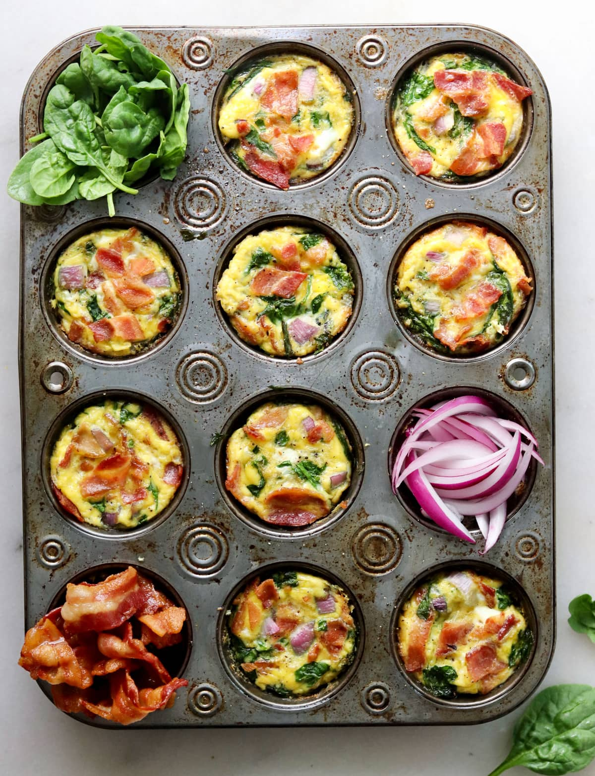 Top down of the cooked individual frittatas in the muffin tin.
