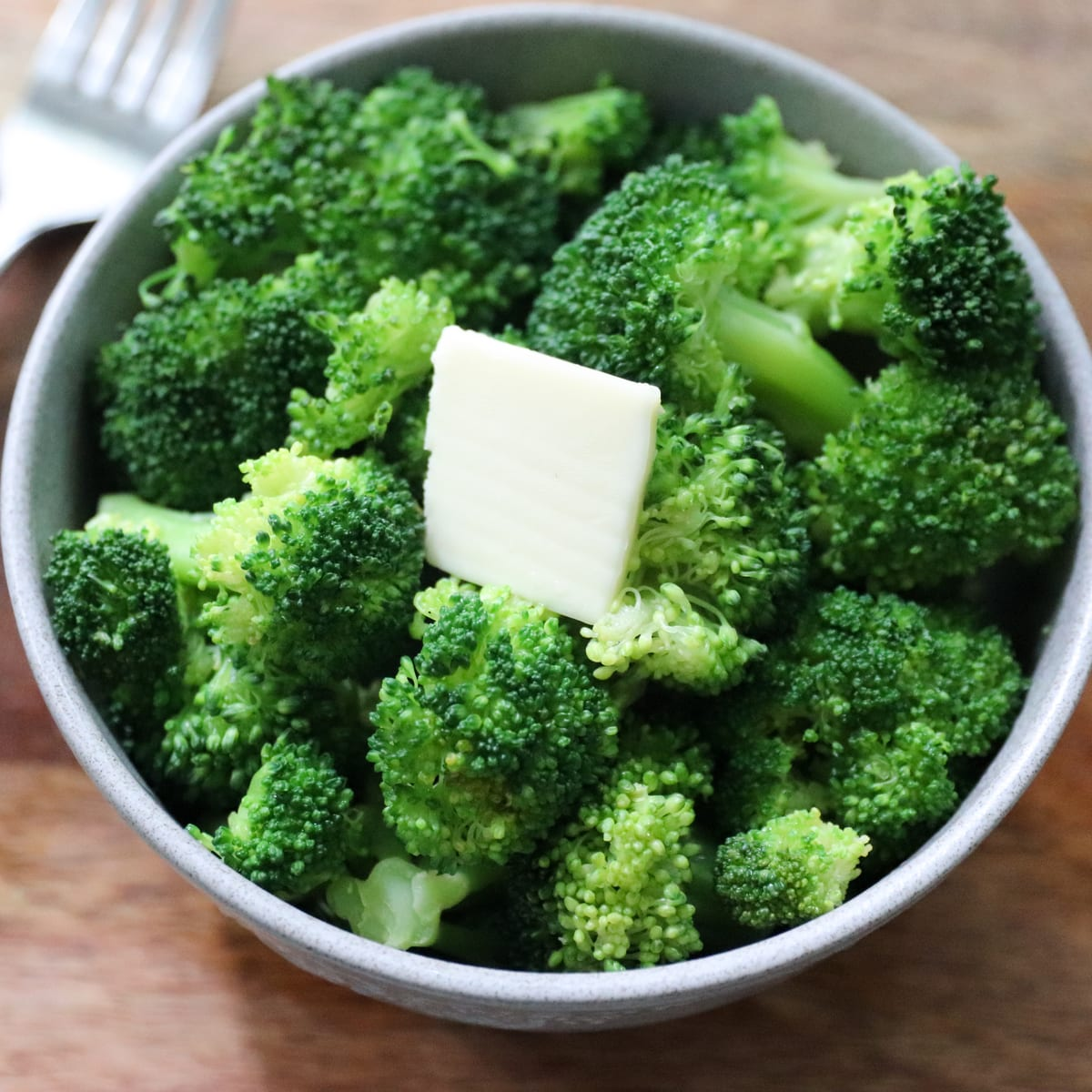 A gray bowl filled with bright green cooked broccoli.