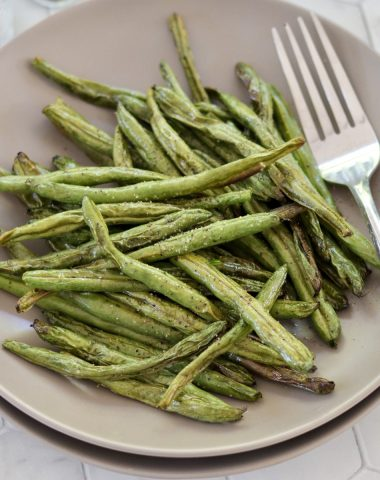 Close up of crispy roasted green beans on a gray plate with a fork.