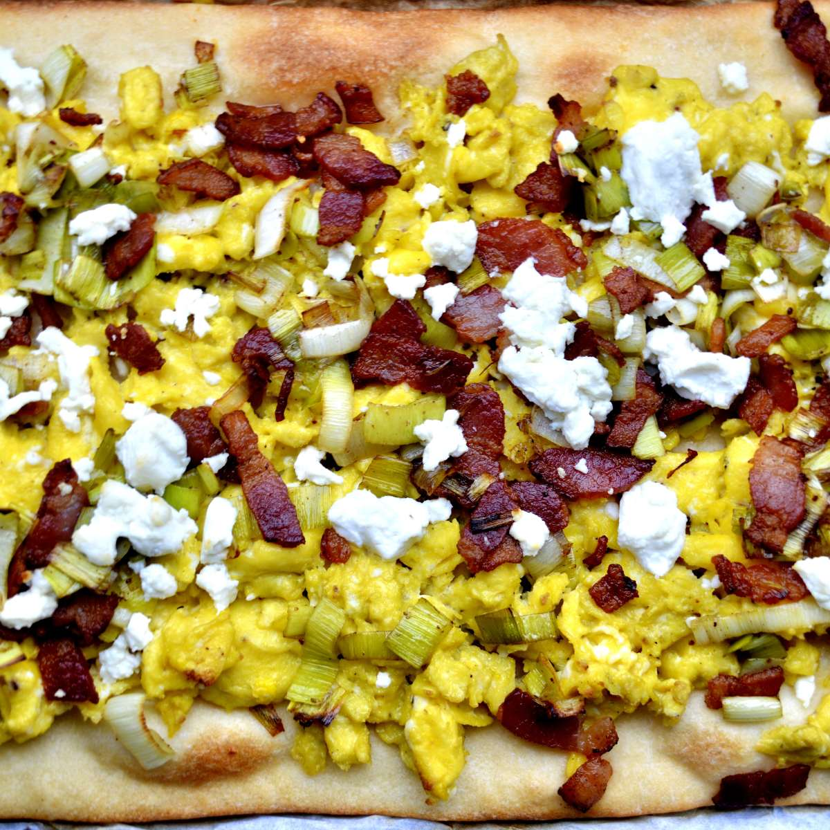 breakfast flatbread with eggs, leeks, and bacon