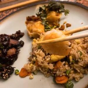 A plate with Shrimp & Pork Fried Rice, Shrimp Dumpling XO, and Honey Roasted Pork with Peanuts. A pair of chopsticks holds a shrimp
