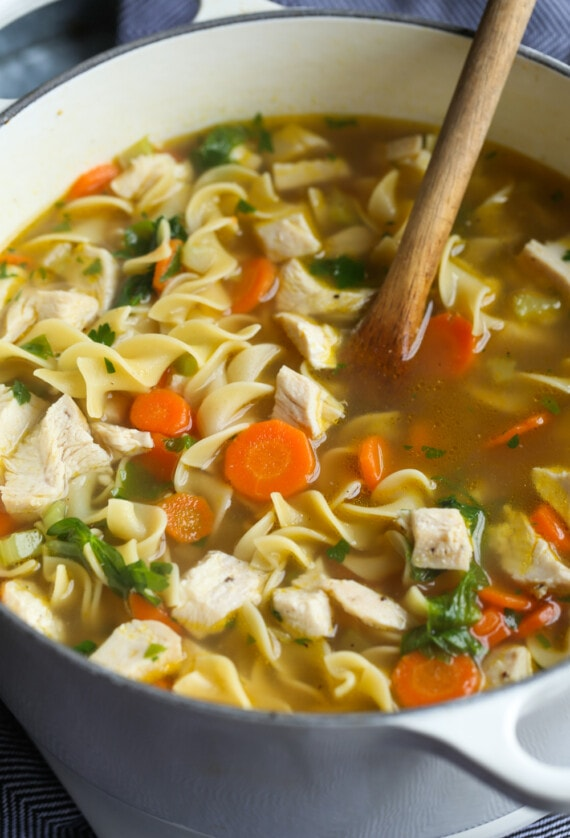 chicken noodle soup in a pot with a wooden spoon