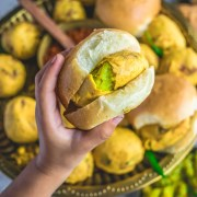 a child holding a Bombay Special Vada Pav in her hand