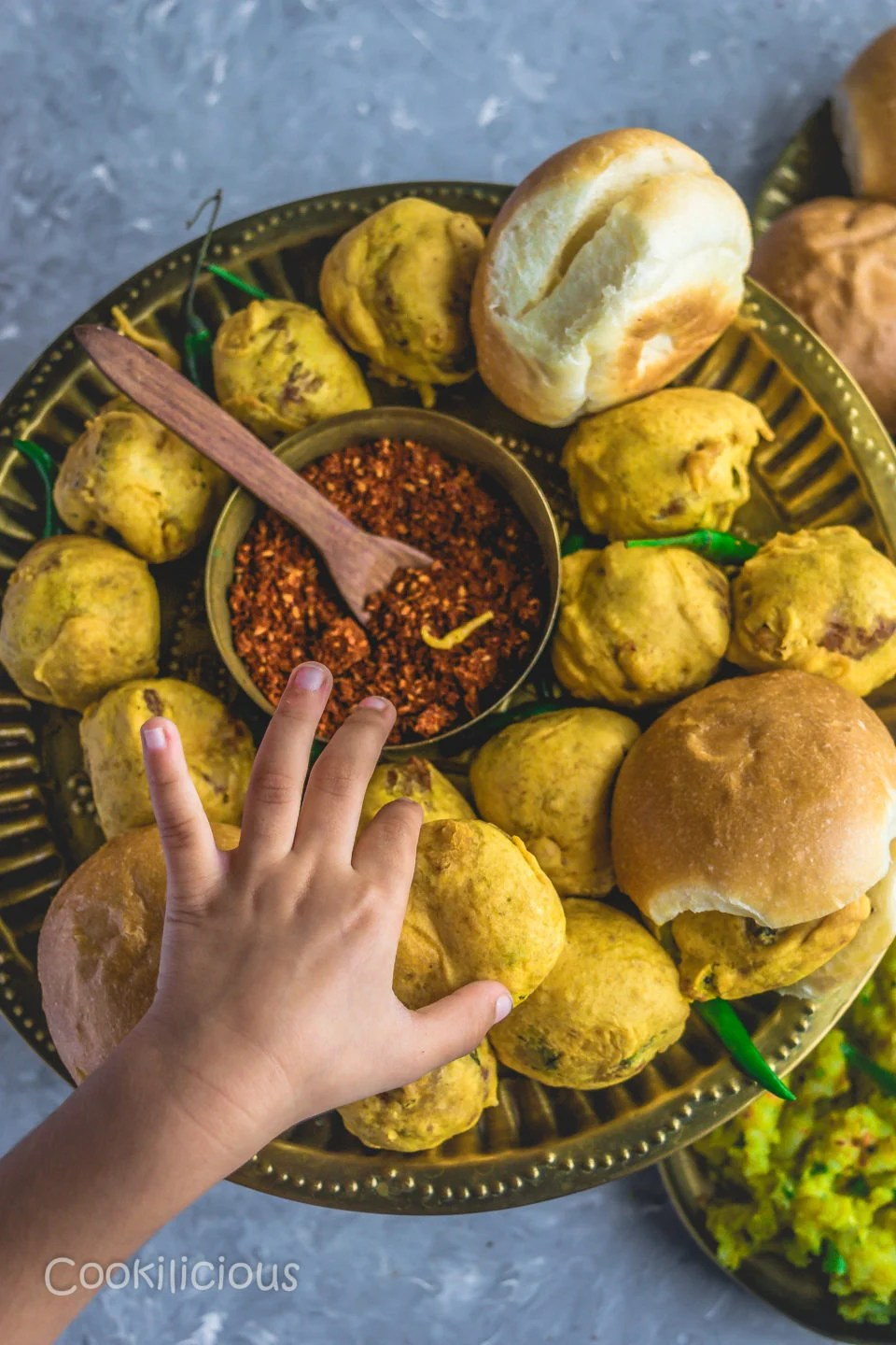 a child's hand reaching out to pick up a vada pav from a plate