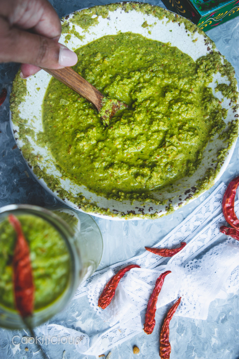 a hand dipping a wooden spoon into a bowl of Indian Green Chutney with Leftover Lettuce Leaves