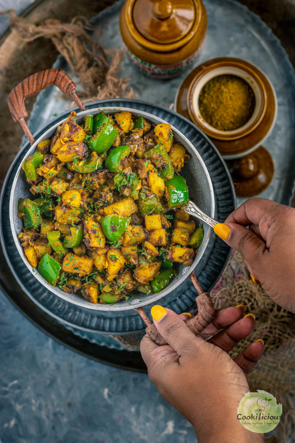 one hand digging a spoon into a kadai of Achari Aloo Capsicum while the other hand is holding the kadai