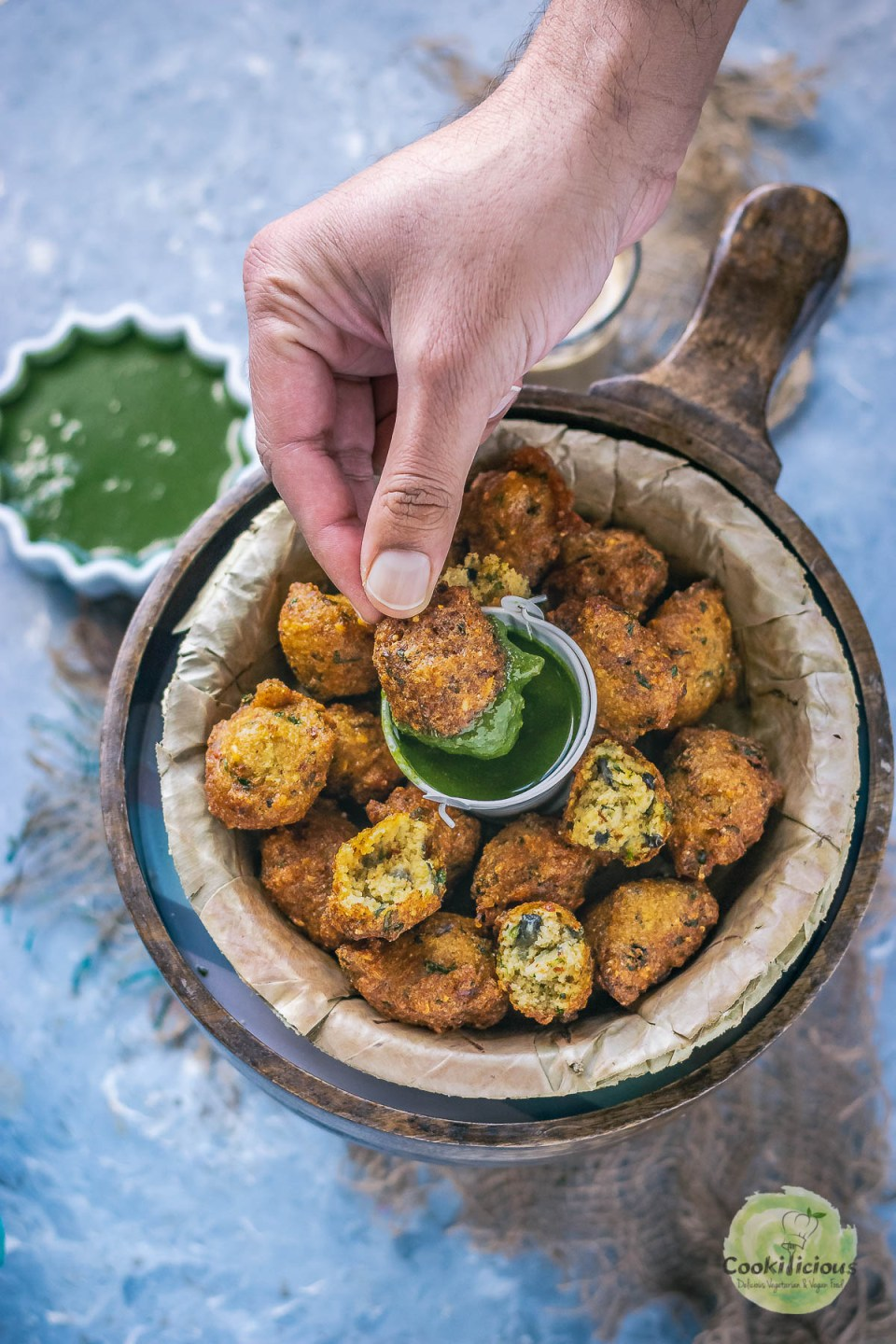 a hand dunking one Crispy Moong Dal Pakora (one of the popular easy vegan appetizers) into a bowl of green chutney