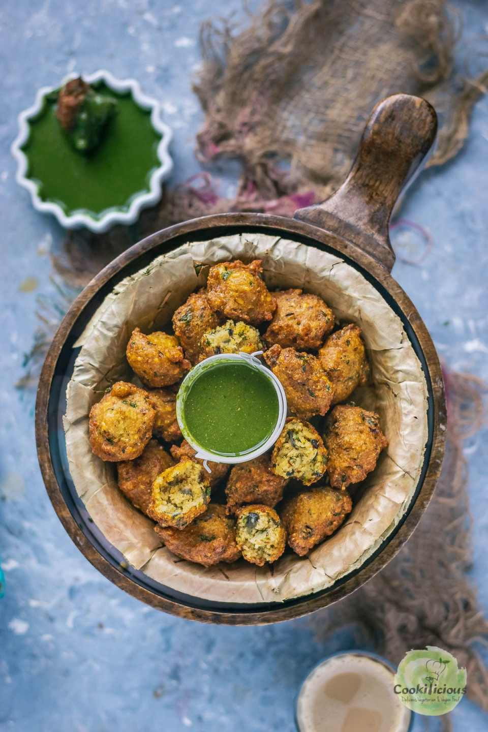 Crispy Moong Dal Pakora which is one of the easy vegan appetizers is placed in a round platter with a bowl of chutney in the middle and next to it