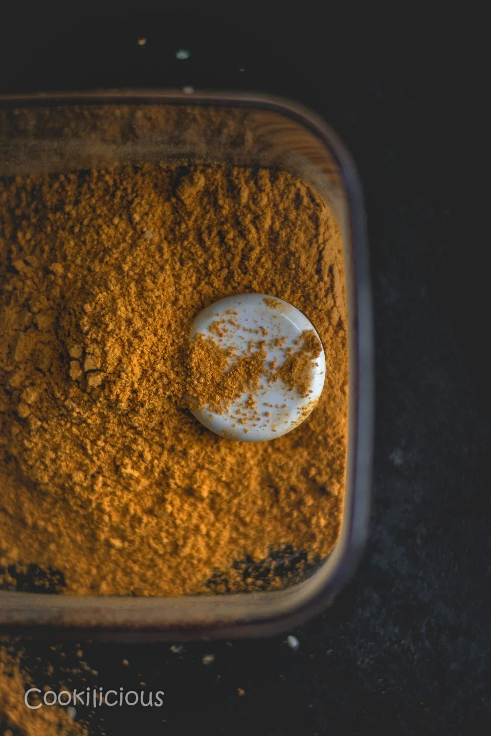 top angle shot of a spice box filled with Molagapudi and a scoop