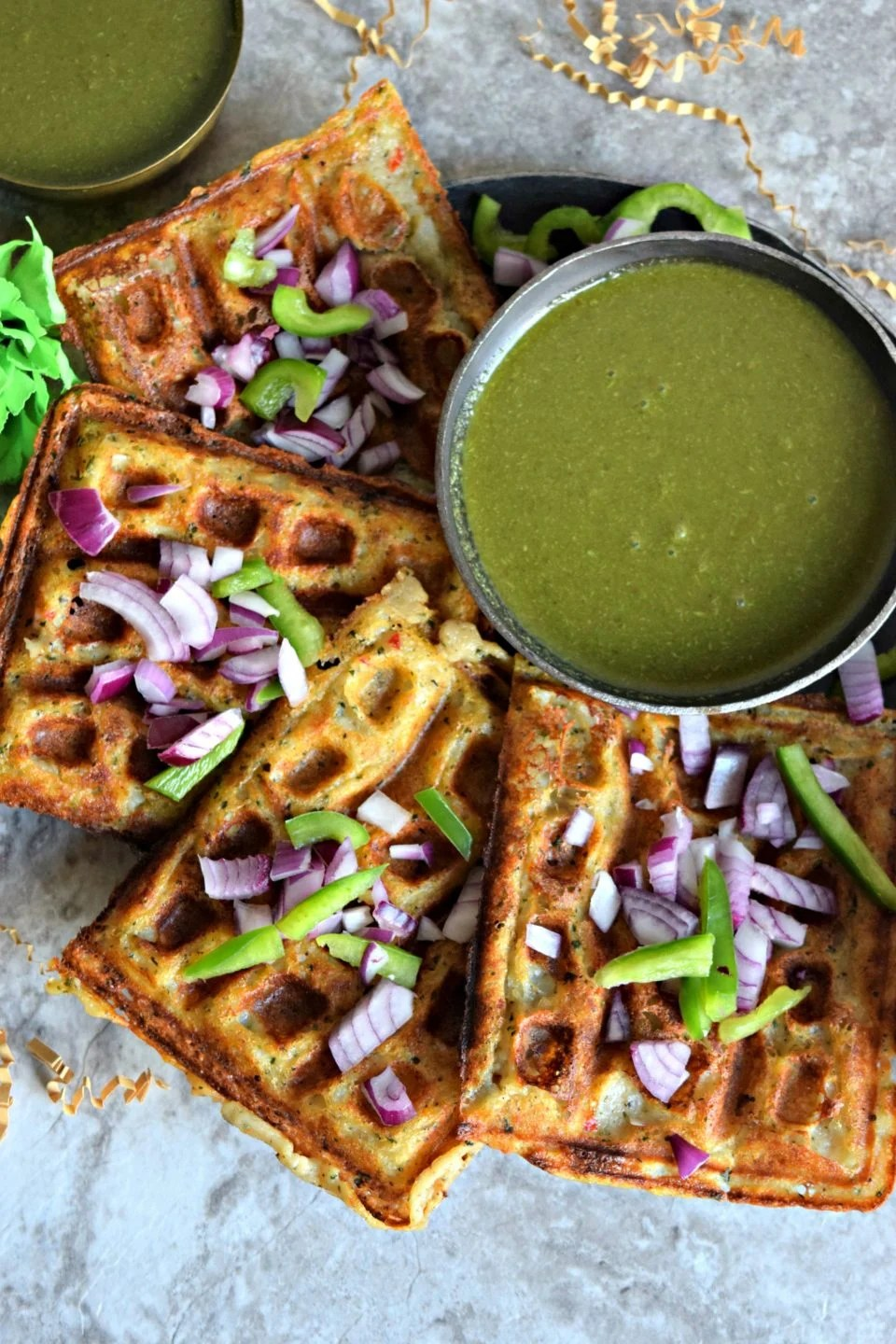 Mashed Potato Hummus Waffles placed one after the other on a round plate with a bowl of chutney next to it