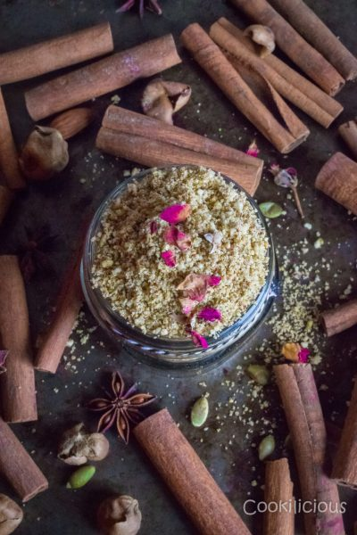 Milk masala served in a glass jar garnished with edible flowers with cinnamon sticks around it.