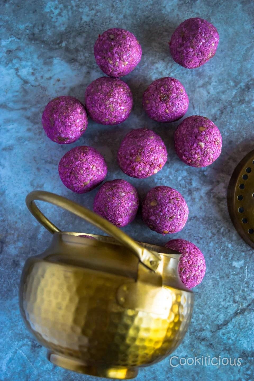 flat lay shot of Frozen Raspberry Date Coconut Balls fallen from a brass bowl