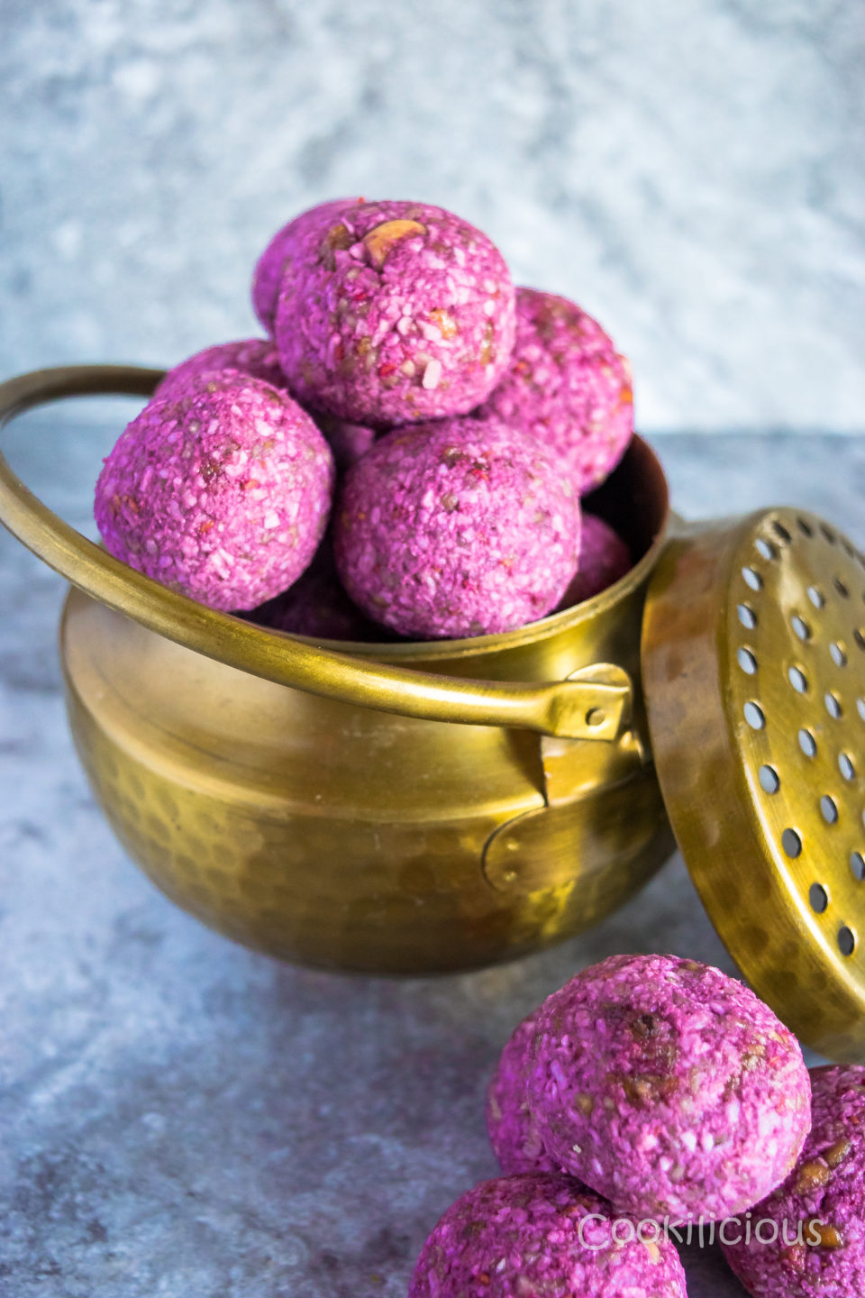 A brass bowl filled with Vegan No Bake Raspberry Energy Bites