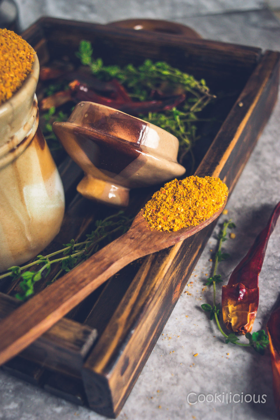 close up side shot of a wooden spoon with sambhar powder resting on a wooden tray
