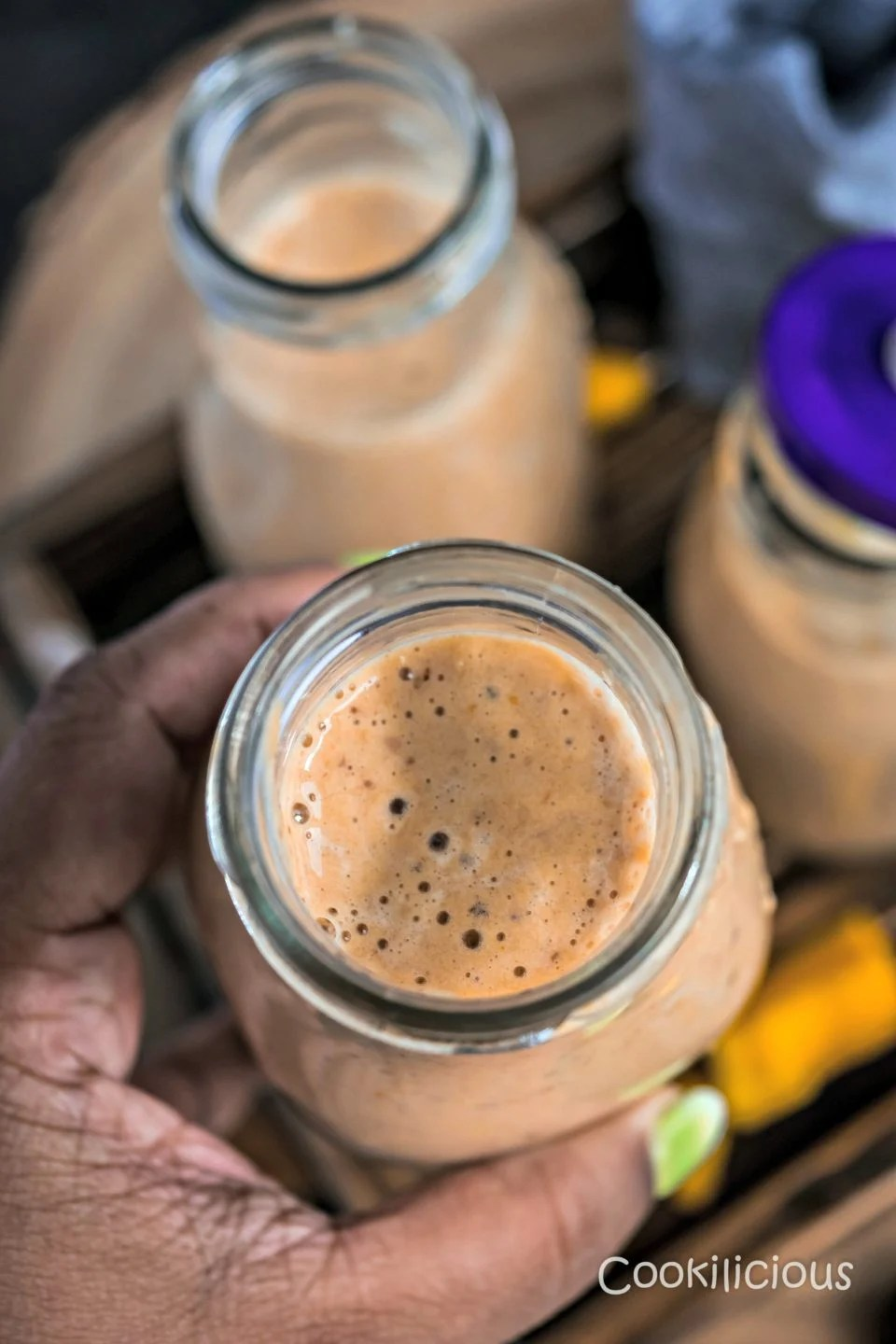 A hand holding a glass of Dairy Free Mango Figs & Apricot Power Smoothie