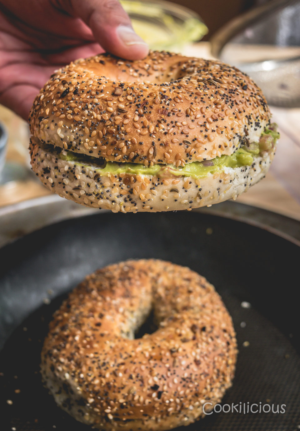 a hand lifting one Bagel Sliders with Homemade Guacamole while the other rests below