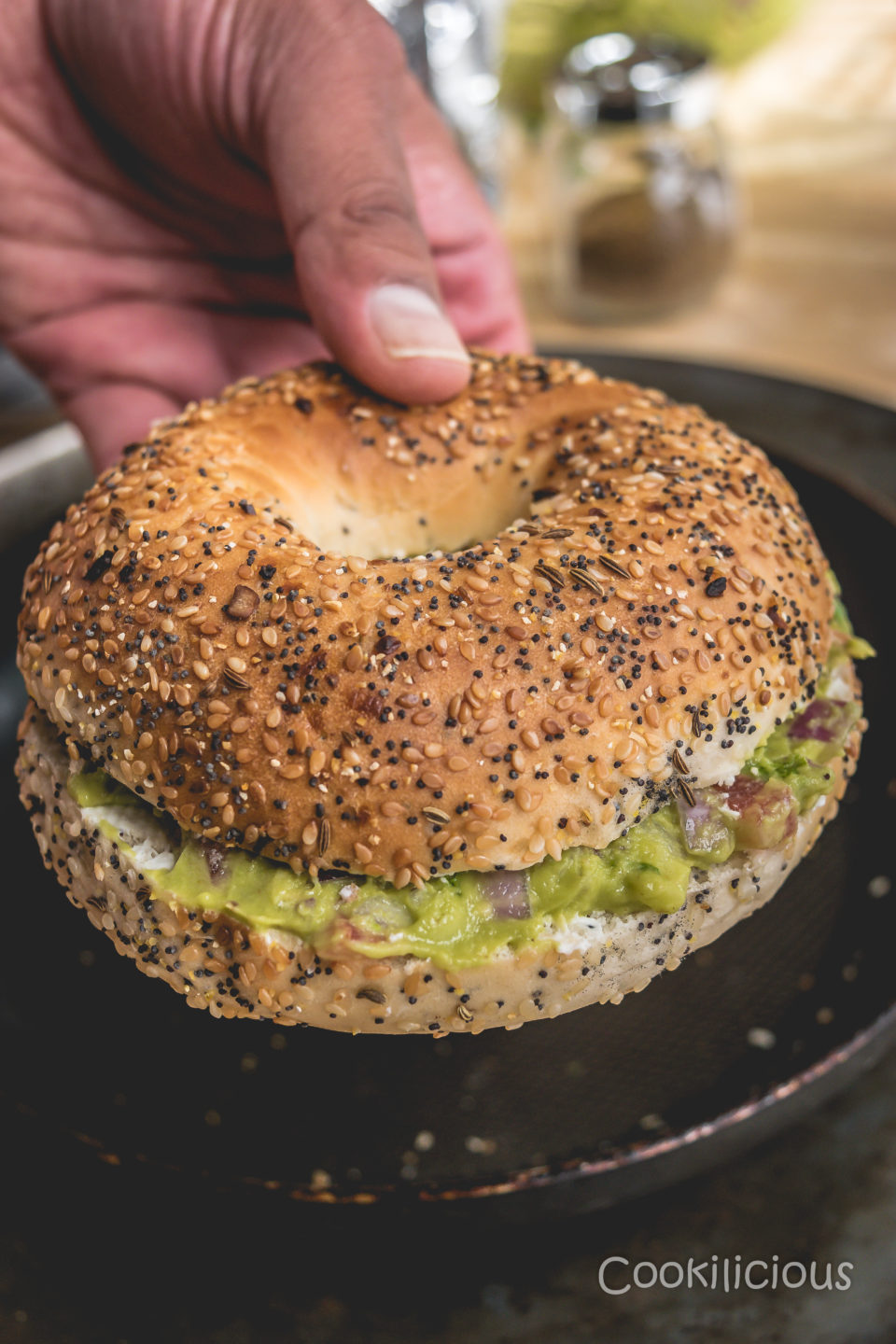 a hand holing one Bagel Sliders with Homemade Guacamole