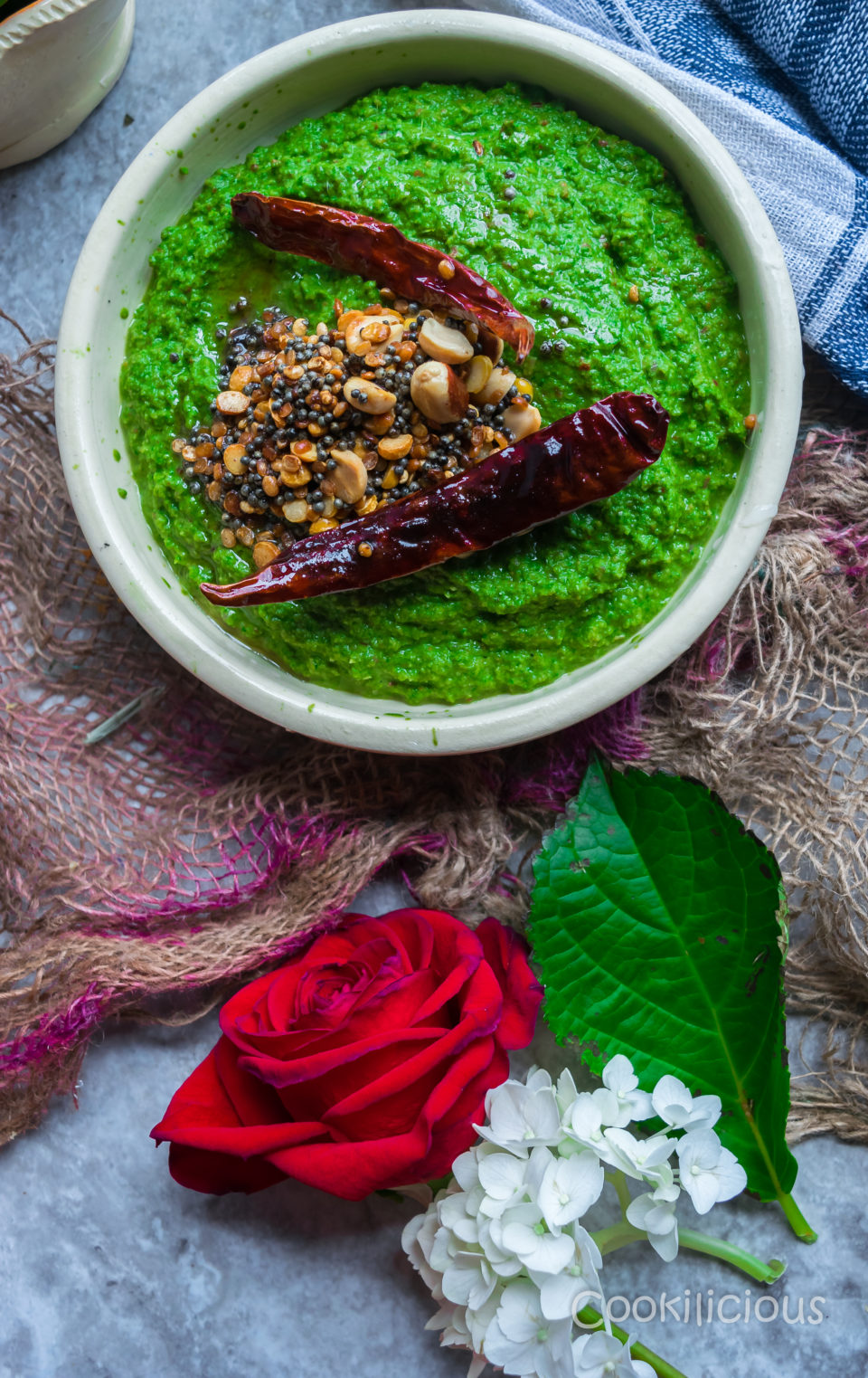 A bowl of Vegan Spinach & Peanut Chutney with tadka on top and a red rose around it.