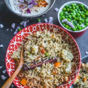 top shot of a bowl filled with Vegetable Pulao in an Instant Pot with a wooden spoon in it and raita and green peas in a bowl.