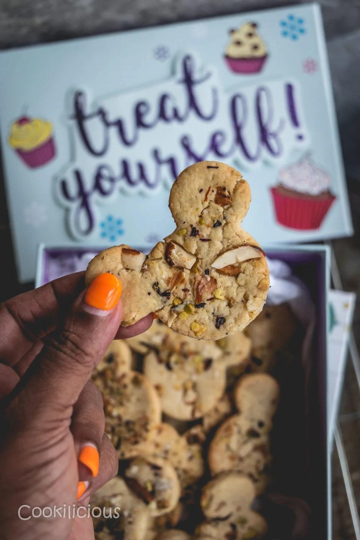 a hand holding one Eggless Kesar Pista Badam Biscuits/Saffron Cashew Almond Cookies