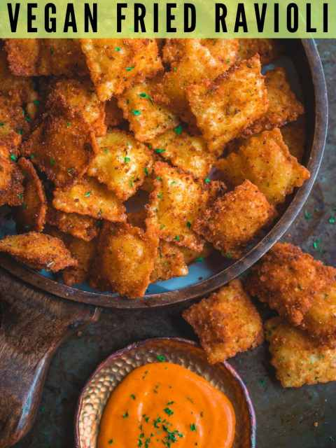 Copycat Olive Garden Cheesy Fried Ravioli in a tray with a dip on the side and text at the top