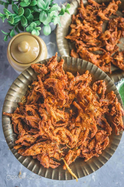 top angle shot of a plate filled with Vegan Crispy Onion Pakoda | Fried Kanda Bhajiya