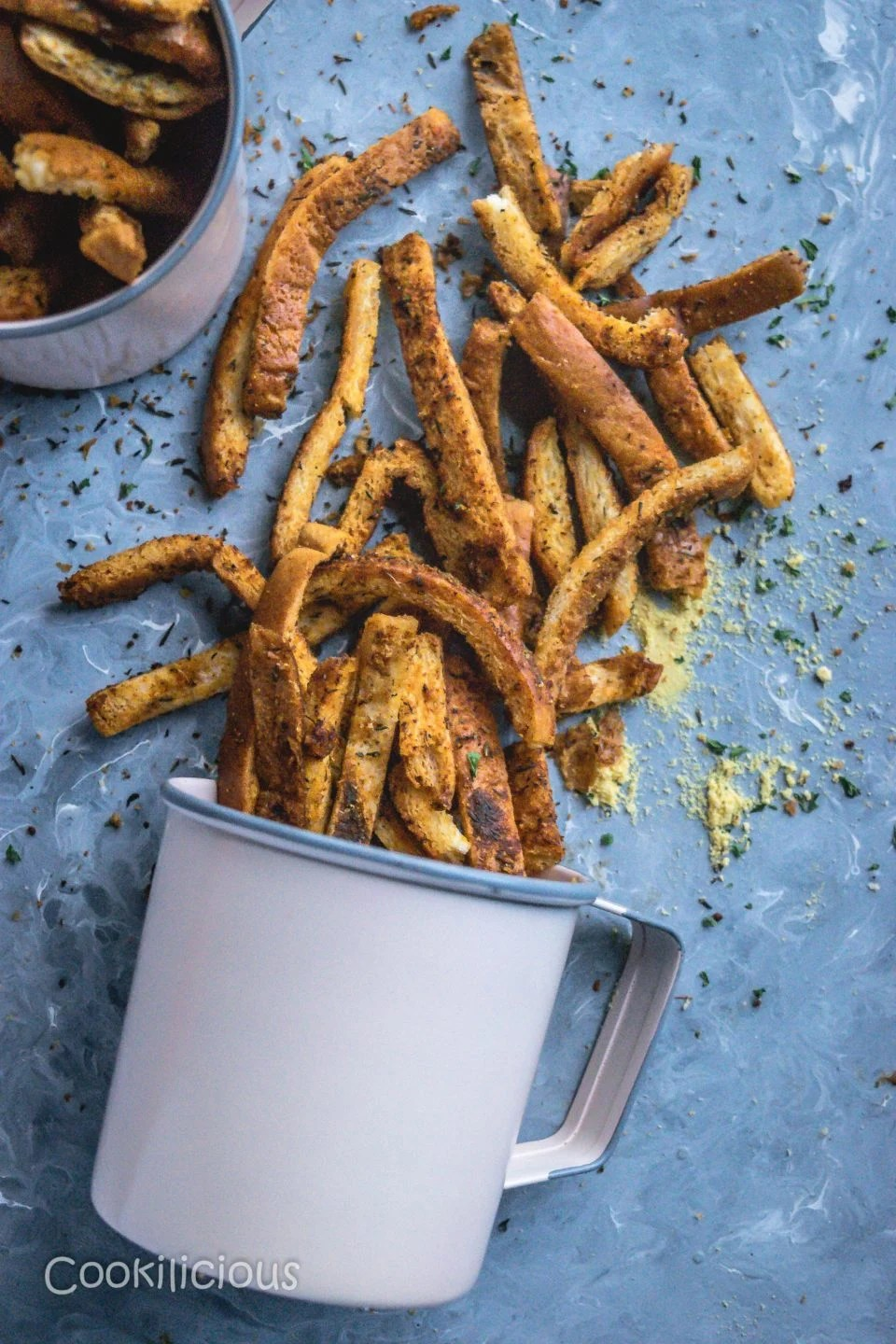 a mug with Crispy Bread Crust Parmesan Baked Fries fallen down and text on top