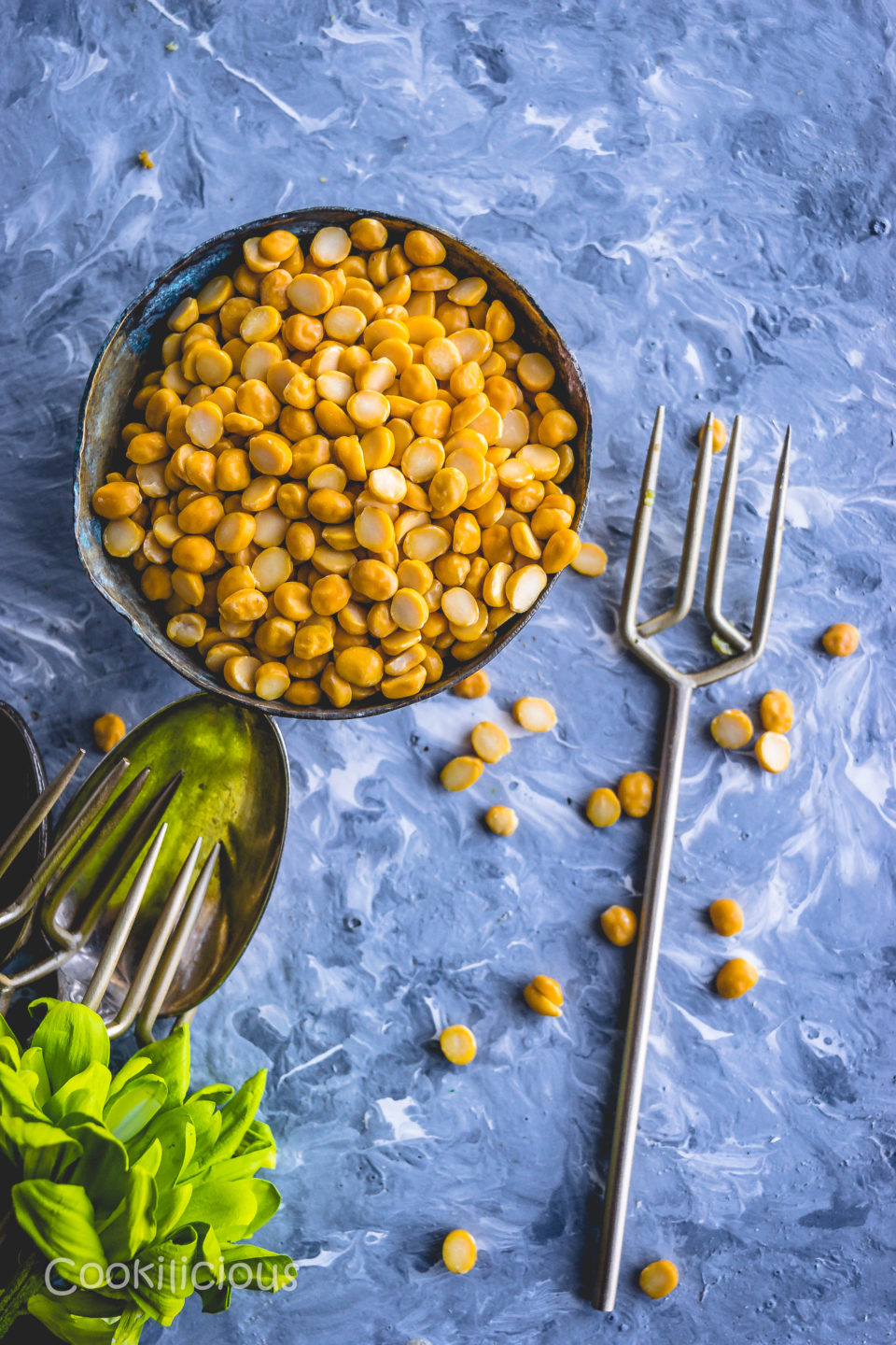chana dal in a bowl with a fork next to it before soaking it to make Steamed Lentil Bafauri