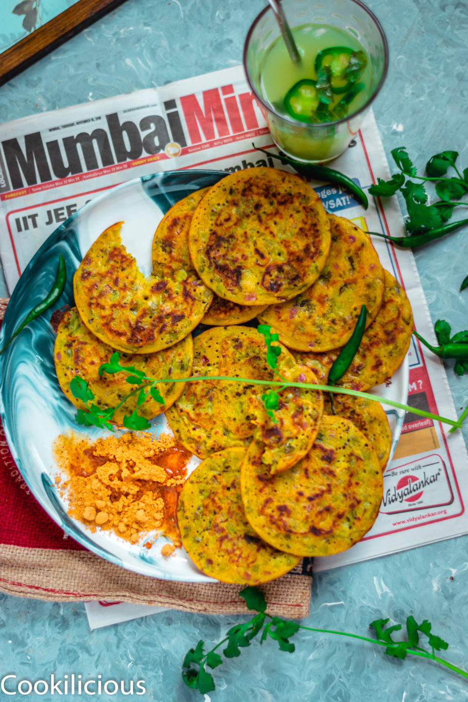 flat lay image of Mini Masala Uttapam on a plate placed over a newspaper