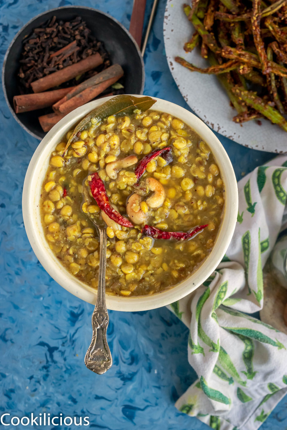a spoon into a bowl filled with Bengali Style Cholar Dal With Chana Dal