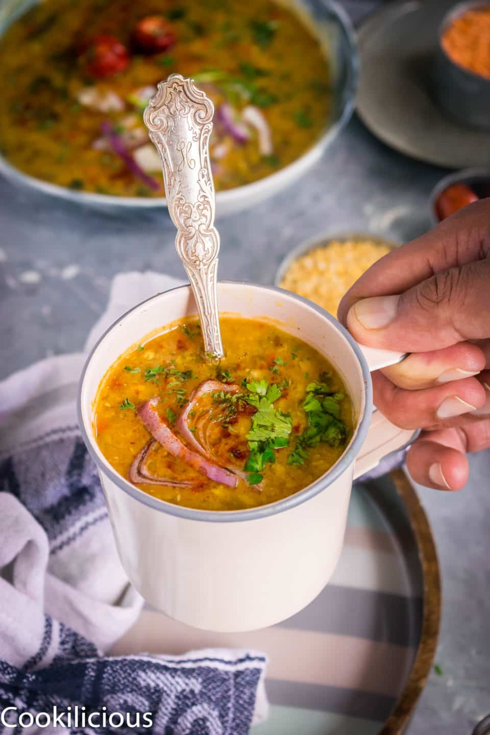 close up shot of a hand lifting a mug filled with Indian Style Green Moong Sprouts Dal Fry