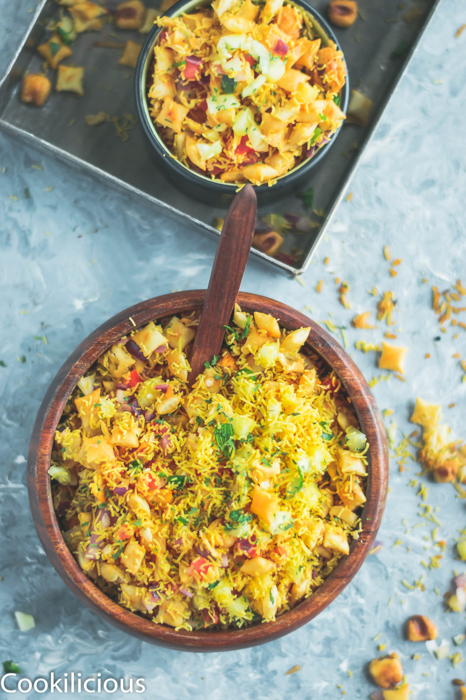 top angle shot of 2 bowls containing Crispy & Masaledar Cheeselings Bhel in a bowl with a spoon in it