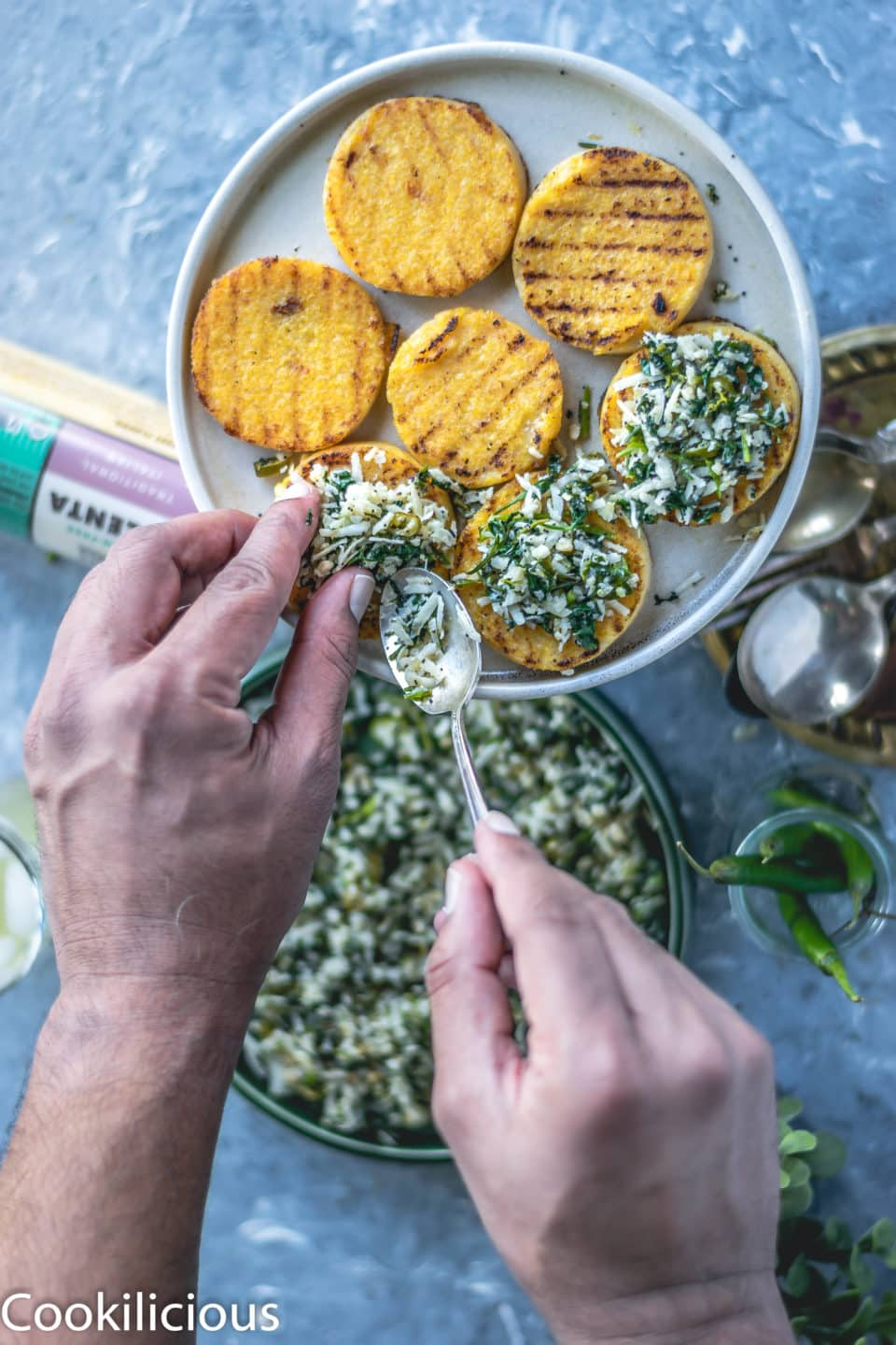 a set of hands spreading the masala over the grilled polenta (vegan gluten free recipes)