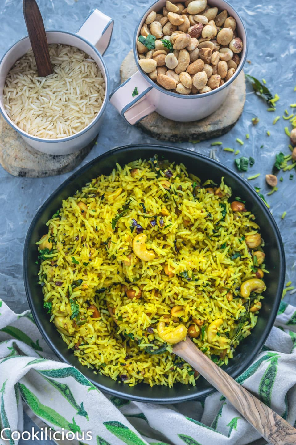 a bowl full of Masale Bhat with a wooden spoon in it and a mug full of rice and another mug filled with peanuts on the side
