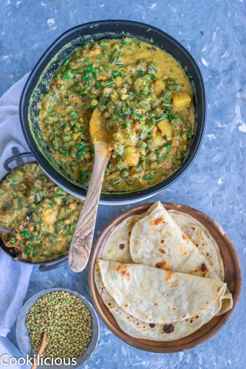 a bowl of Green Beans & Potato Gravy resting next to a plate full of chapati