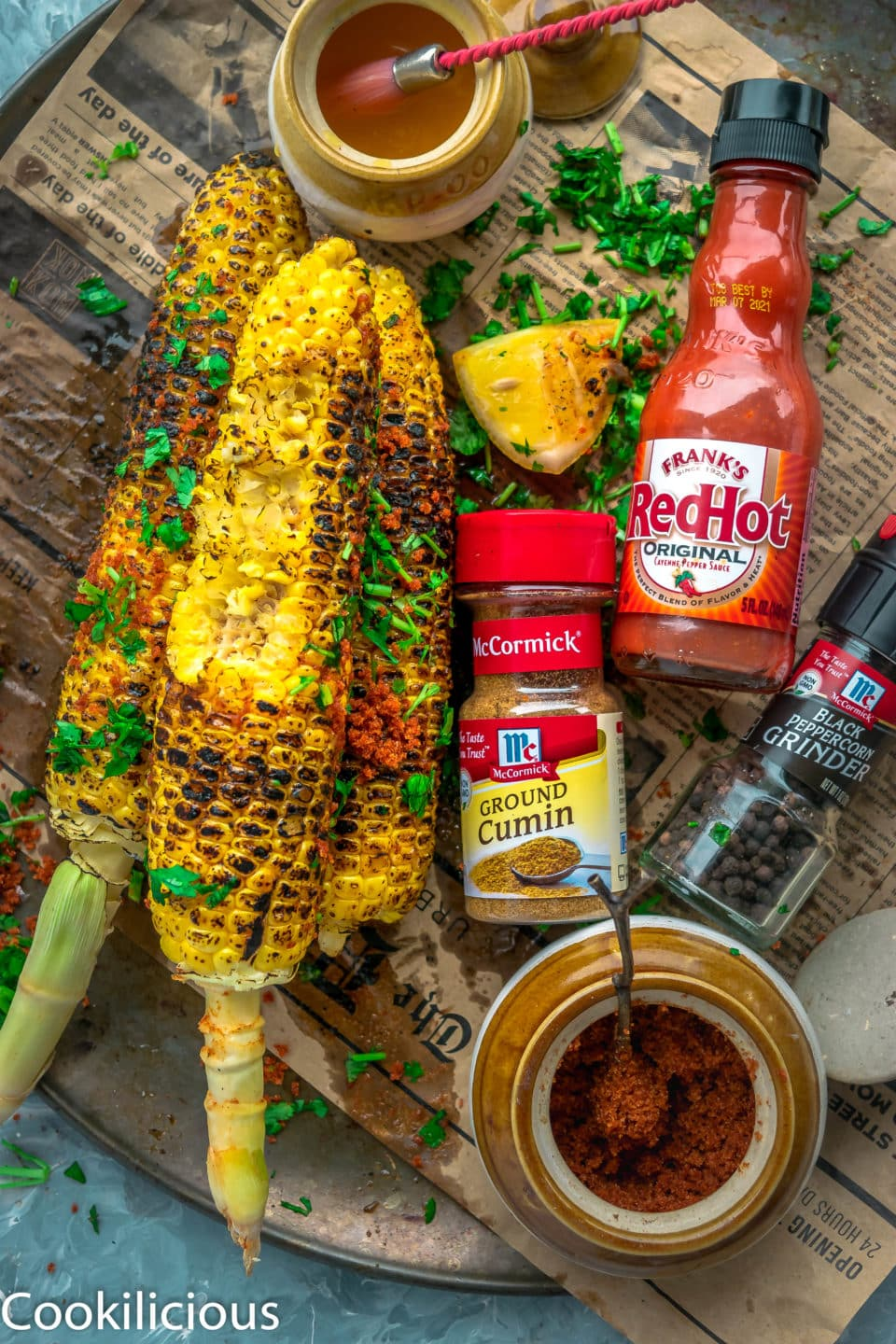top angle shot of Indian Street Style Corn On The Cob with one of it half eaten and a lemon wedge on the side