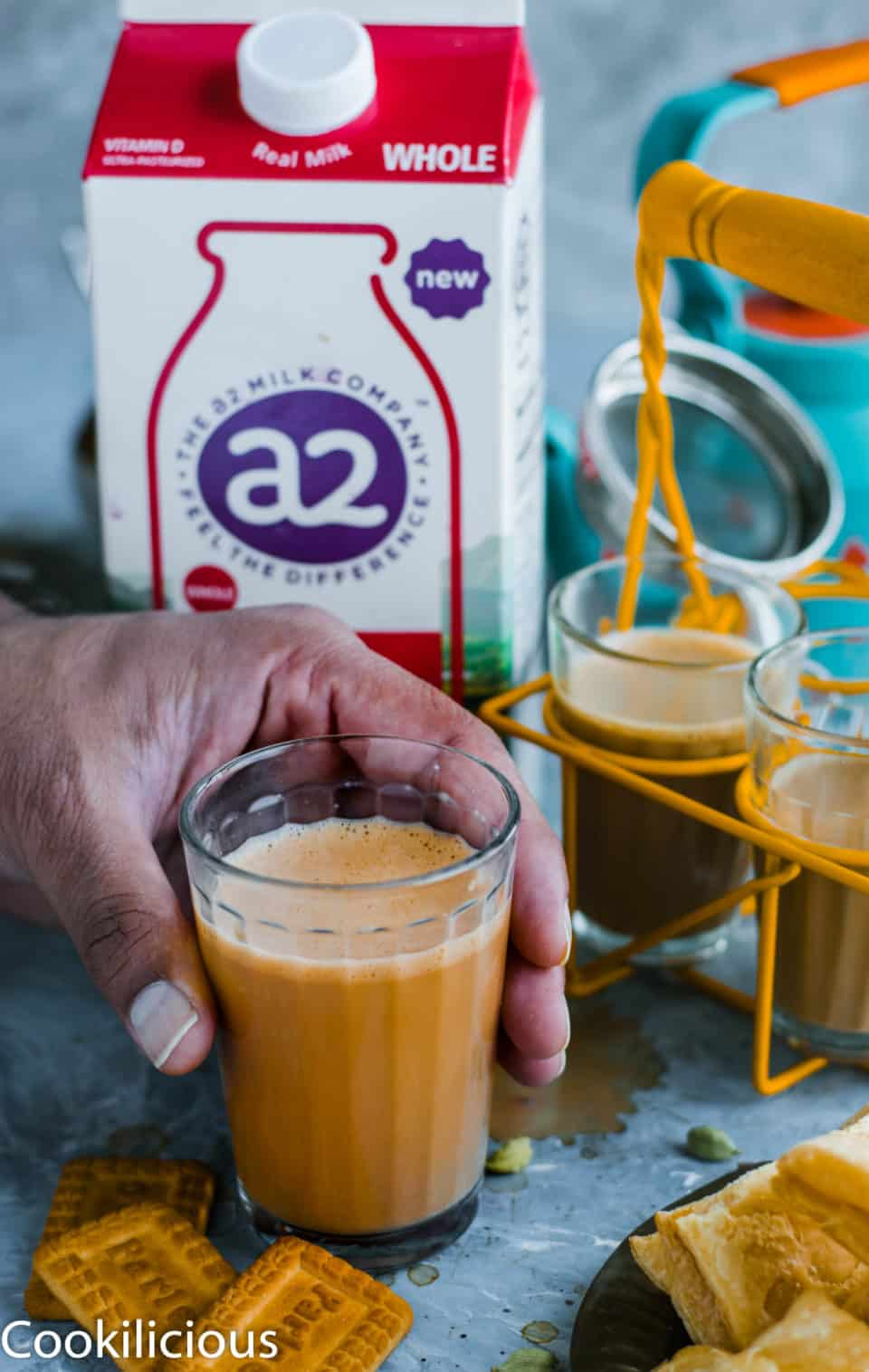 a hand holding a glass of masala chai with a2 milk in the background