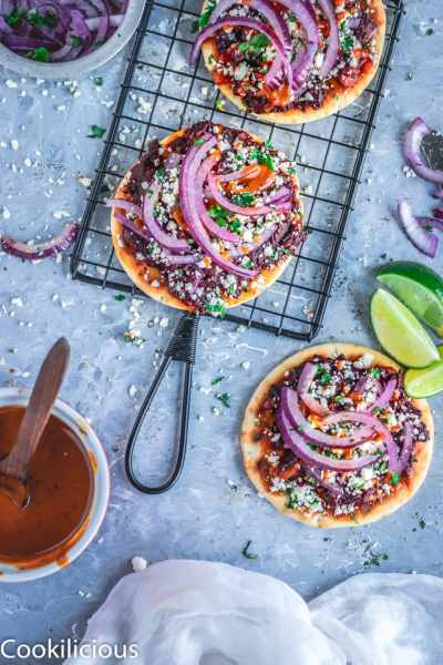 Grilled Dabeli (Made With Potatoes & Beets) Pita Bread Pizza on a wire rack with one on the side