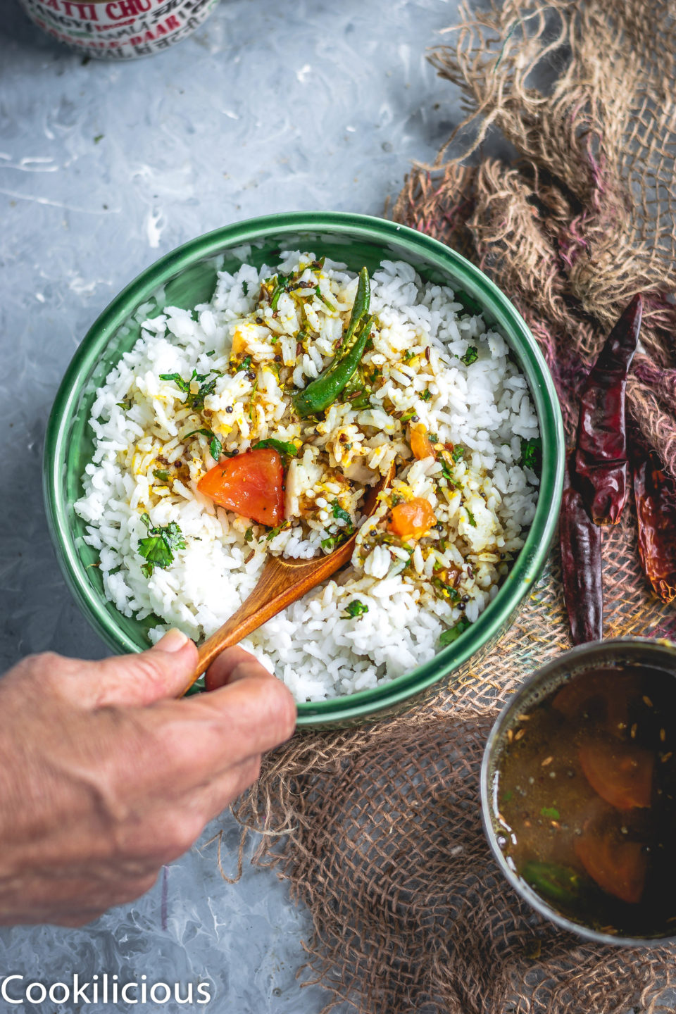 a hand mixing South Indian Tomato Rasam With Pink Lentils with rice in a bowl with a spoon