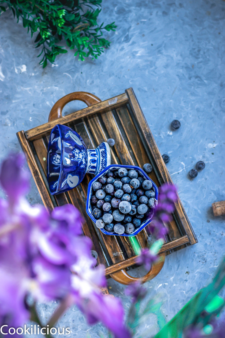 frozen blueberries in a bowl placed on a tray used to make Blueberry Masala Soda Ice Pops