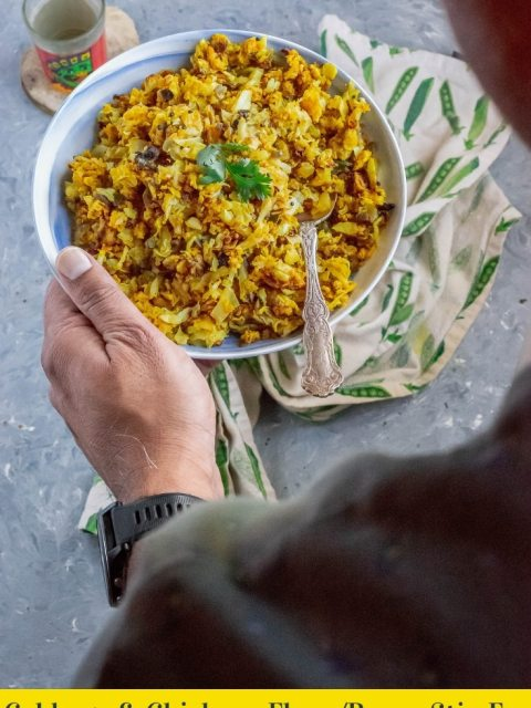 pair of hands holding a bowl of Cabbage & Chickpea Flour/Besan Stir-Fry & text at the bottom