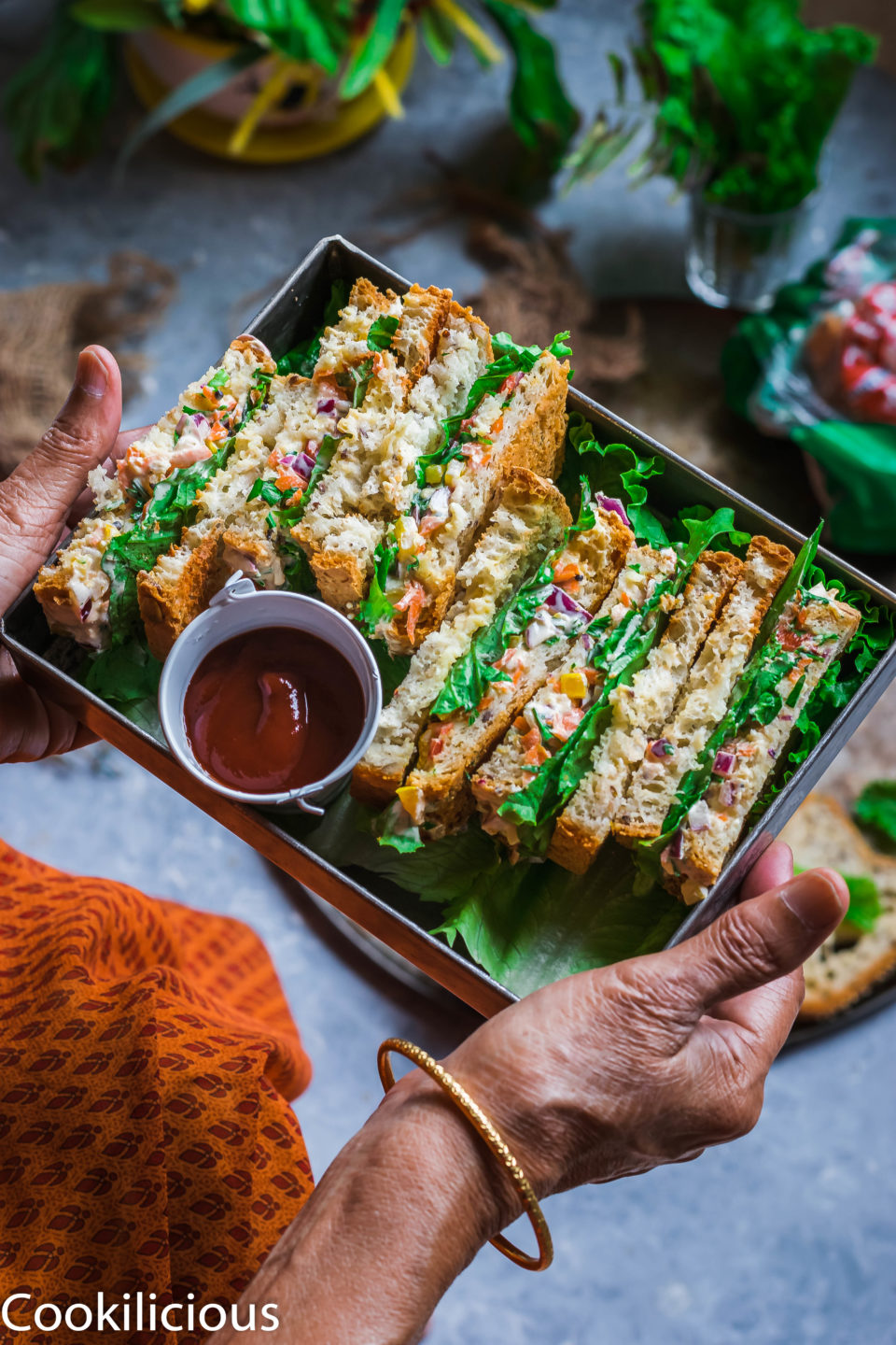 a set of hands holding a tray filled with Indian Style Spiced Yogurt Sandwiches