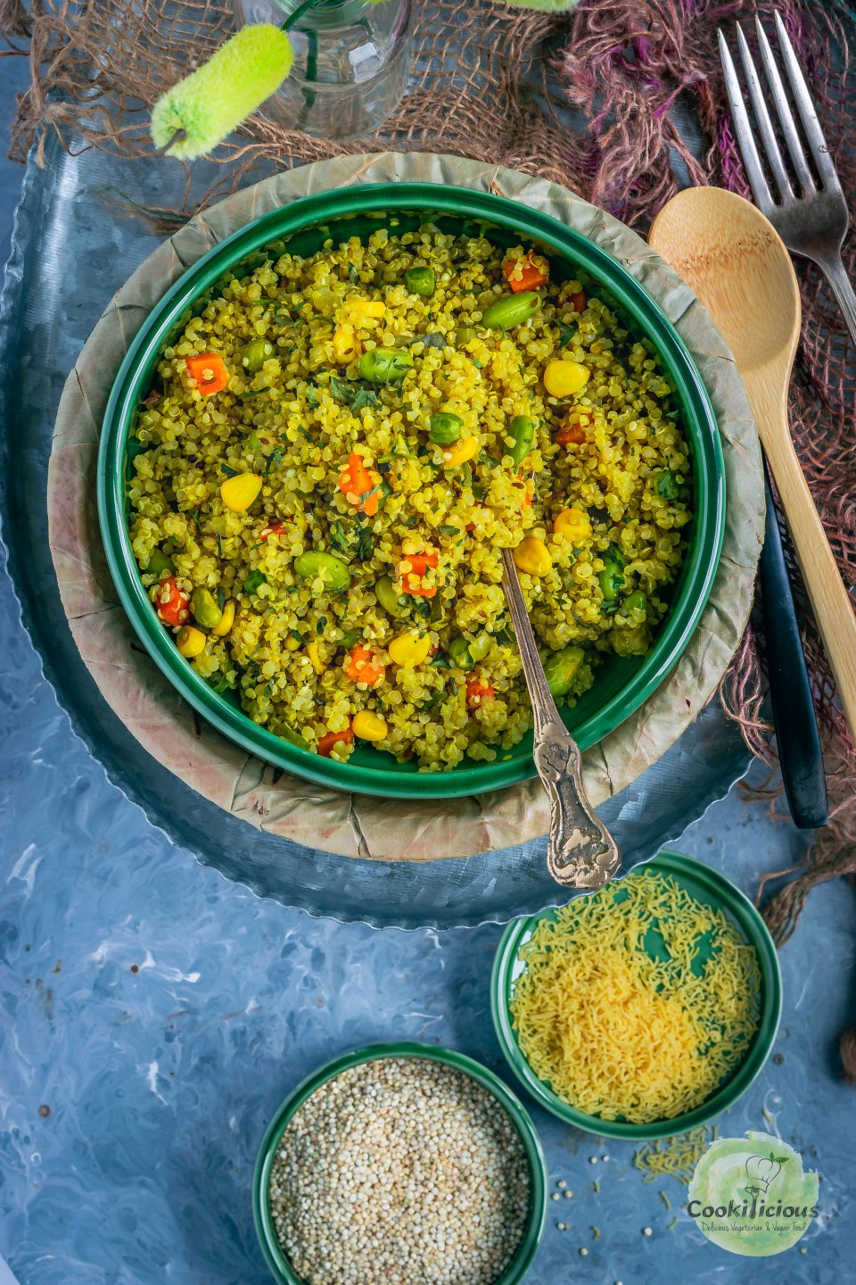 a bowl filled with Vegetable Quinoa Upma with a spoon in it and few spoons on the side